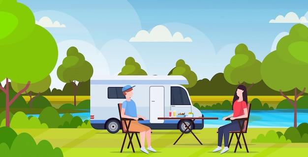 Coppia seduta al tavolo vicino campeggio famiglia rimorchio camion caravan auto uomo donna spendendo togeher estate vacanze concetto beautful natura paesaggio sfondo piatto lunghezza orizzontale