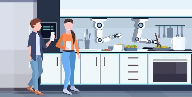 Coppia utilizzando l'applicazione mobile che controlla il robot pratico astuto del cuoco unico che prepara orizzontale moderna interna interna della cucina di concetto di intelligenza artificiale dell'innovazione dell'assistente robot dell'omelette delle uova fritte