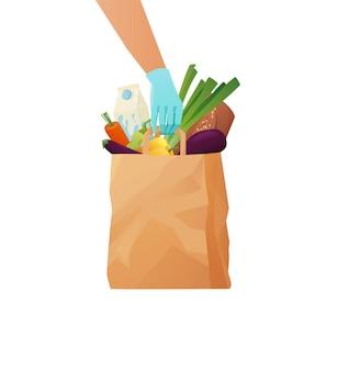 Mano guantata dei corrieri che tiene una borsa ecologica di carta con generi alimentari. consegna o donazione di cibo