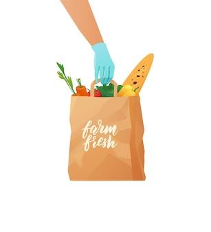 Mano guantata dei corrieri che tiene una borsa ecologica di carta con generi alimentari.