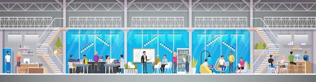 Centro di co-working creativo in stile loft. giovani sorridenti che lavorano ai computer portatili nell'area di lavoro congiunto. open space moderno o ambiente di lavoro condiviso.