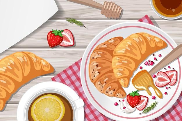 Croissant alla fragola e una tazza di tè al limone in tavola