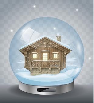 Sfera di cristallo di natale con una casa