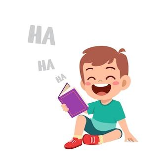 Cule ragazzino legge la storia di un libro divertente e ride così forte