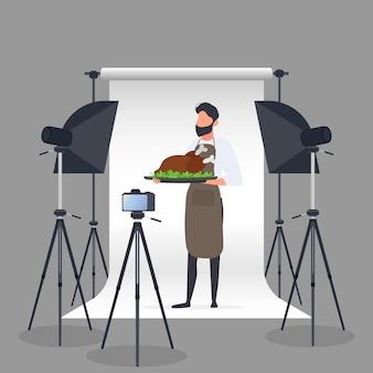 Blogger culinario. un uomo con un grembiule da cucina tiene un pollo fritto su un vassoio. fotocamera su treppiede, softbox. blog culinario o concetto di vlog. vettore.
