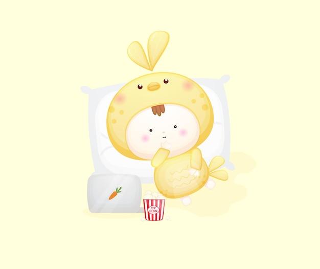 Bambino carino in costume da uccello sdraiato e guardando film. illustrazione dei cartoni animati vettore premium