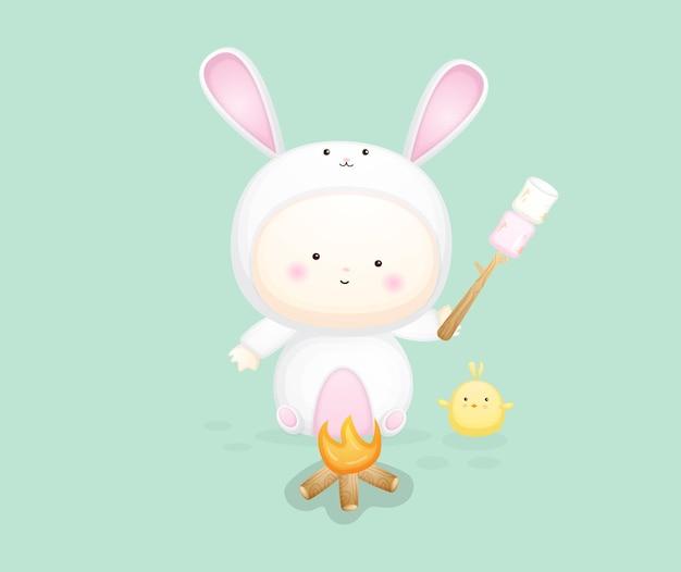 Bambino sveglio in costume da coniglietto che tiene marshmallow. illustrazione dei cartoni animati vettore premium