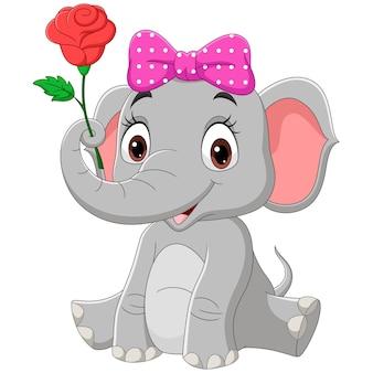 Ragazza sveglia dell'elefante del bambino che si siede con un fiore