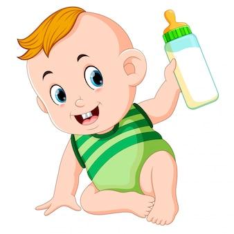 Il bambino carino che gioca e tiene in mano la bottiglia del latte