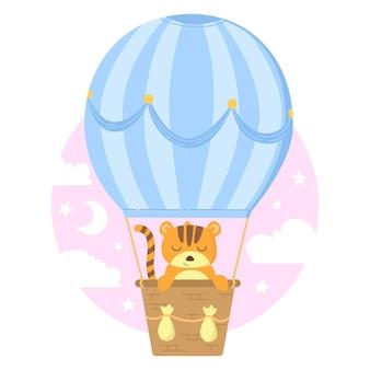 Simpatico tigrotto nel cesto che scuoia sul palloncino blu tra il cielo rosa con nuvole