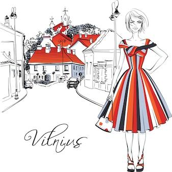 Ragazza carina bella moda in abito estivo sulla tipica strada nel centro storico di vilnius, lituania.