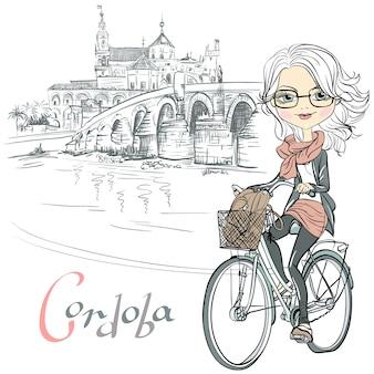 Carina bella ragazza alla moda va in bicicletta a cordoba, andalusia, spagna. moschea mezquita e ponte romano sullo sfondo