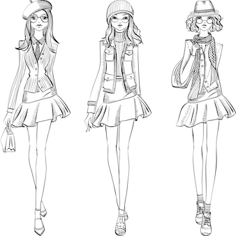 Ragazze carine belle hipster alla moda in giacche, gonne e berretti con borse.