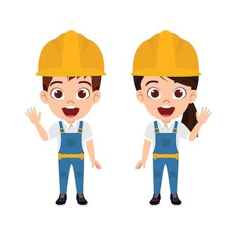 Carattere del ragazzo e della ragazza dell'operaio edile del bambino bello sveglio in piedi e che fluttua con gli abiti dell'operaio di costruzione isolati