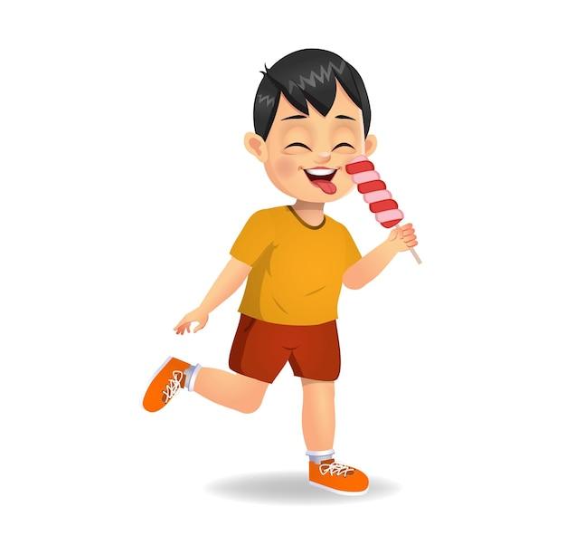 Il bambino sveglio del ragazzo mangia la caramella. isolato