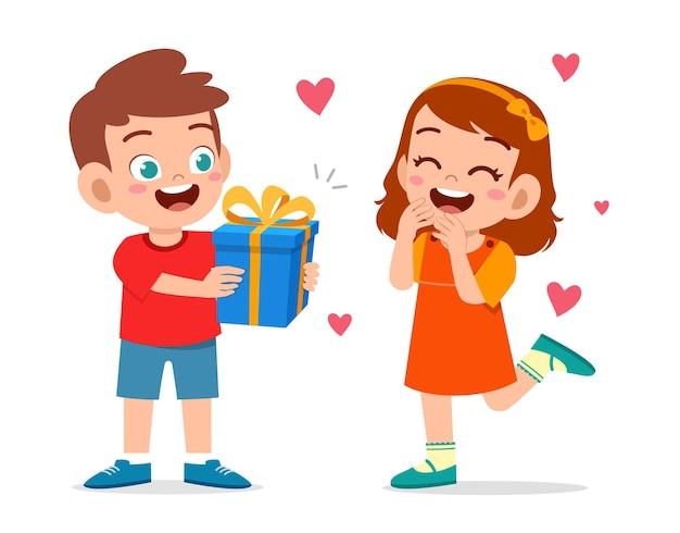 Il ragazzo sveglio dà presente alla bambina per festeggiare il compleanno Vettore Premium