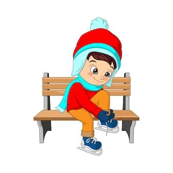 Ragazzo carino in abiti invernali seduto su una panchina, ragazzino che si allaccia i lacci delle scarpe