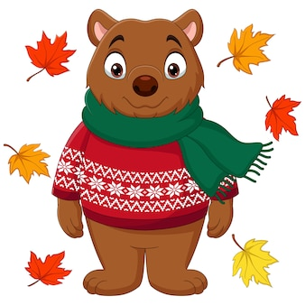 Simpatico orso bruno in un maglione e sciarpa con foglie d'autunno
