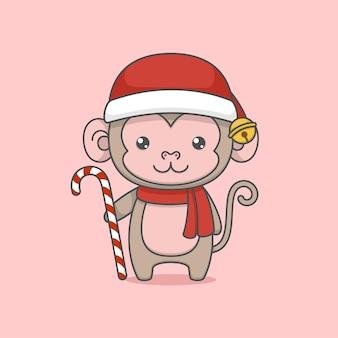 Simpatico cartone animato scimmia di natale che tiene un bastoncino di zucchero