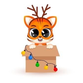 Un simpatico cucciolo di tigre cartone animato si trova in una grande scatola con ghirlande. concetto di natale, capodanno cinese, un simbolo del 2022. adesivo alla moda. biglietto natalizio. illustrazione vettoriale isolato su sfondo bianco.