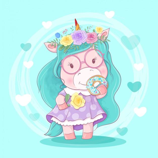 Ragazza unirog del fumetto sveglio in una corona di fiori e una ciambella con glassa.