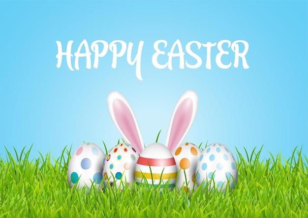 Simpatico biglietto di auguri di pasqua con uova e coniglietto immerso nell'erba