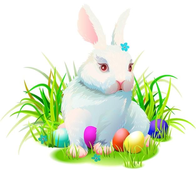 Il coniglietto sveglio del coniglio di pasqua si siede sull'erba verde e sulle uova dipinte