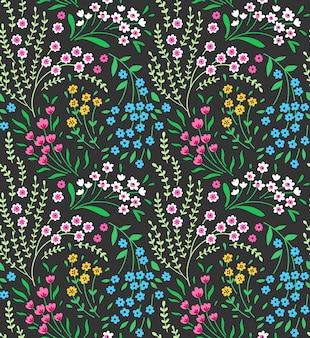 Simpatico motivo floreale nei piccoli fiori colorati. trama senza soluzione di continuità. sfondo verde.