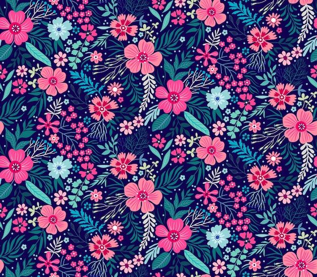 Simpatico motivo floreale nei piccoli fiori. stampa ditsy. trama senza soluzione di continuità. modello elegante per stampe di moda. stampa con piccoli fiori colorati. sfondo blu scuro.