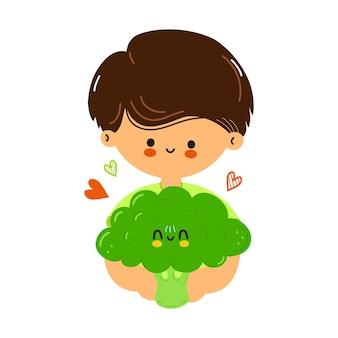 Il ragazzo carino e divertente tiene in mano i broccoli