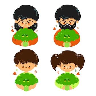 La famiglia simpatica e divertente tiene in mano i broccoli