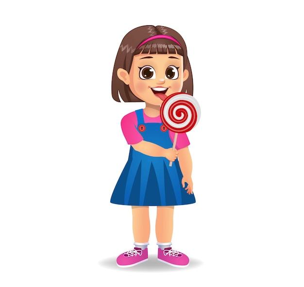 La bambina carina mangia le caramelle. isolato