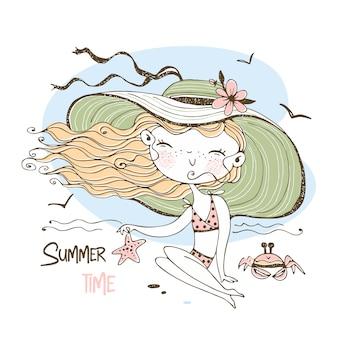 Una ragazza carina in un cappello e costume da bagno sta prendendo il sole sulla spiaggia.