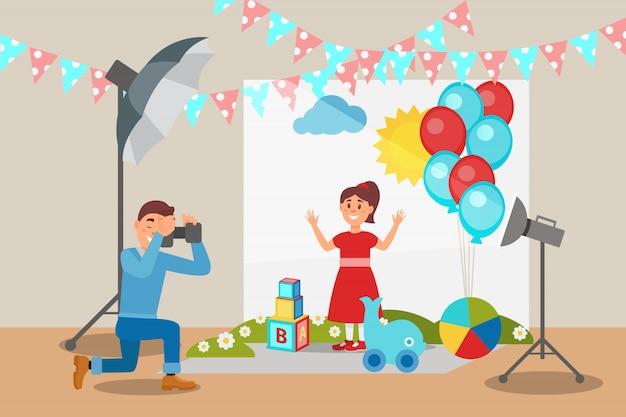 Ragazza sveglia in vestito rosso che posa alla sessione di foto, fotografo che fa le foto, interno dello studio della foto con l'illustrazione dell'attrezzatura professionale
