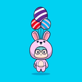 Ragazza carina che indossa il costume da coniglietto galleggiante con palloncino decorativo uovo di pasqua