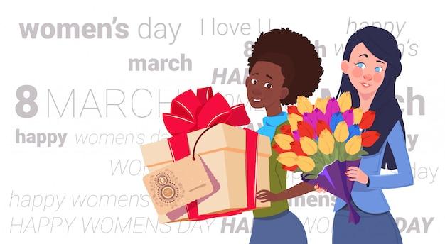 Ragazze sveglie che tengono il contenitore di regalo e mazzo dei fiori durante la festa creativa dell'8 marzo del fondo felice di giorno delle donne festa