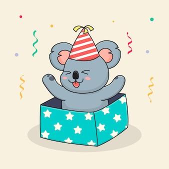 Koala sveglia di buon compleanno dentro la scatola e un cappello