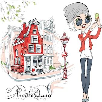 Ragazza carina hipster fa selfie, strada ad amsterdam con la tradizionale casa olandese e lampione sullo sfondo, olanda, paesi bassi.