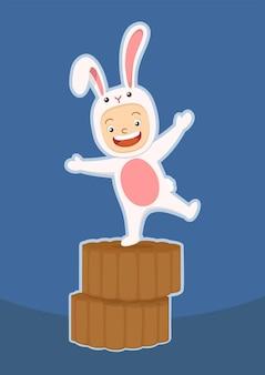 Ragazzo carino in costume da coniglio sul mooncake del festival di metà autunno