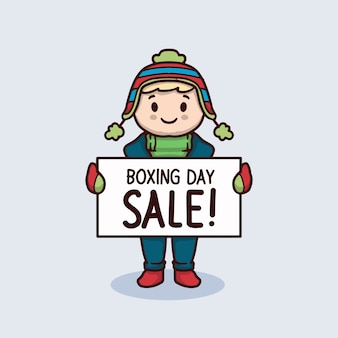 Ragazzo carino con abbigliamento invernale tenere banner di vendita di boxe day