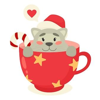 Gattino sveglio in una tazza. tema natalizio, animale da compagnia.