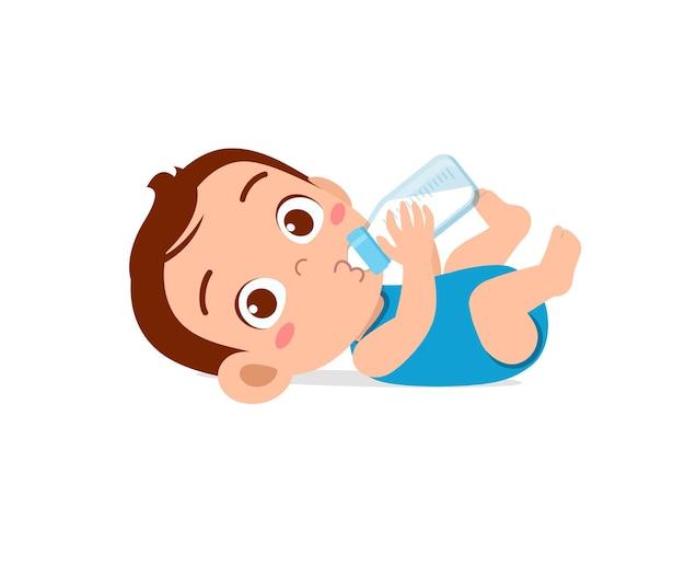 Il piccolo bambino sveglio beve il latte dalla bottiglia