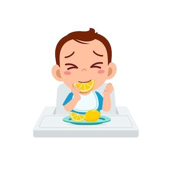 Il piccolo bambino sveglio mangia frutta e limone acido