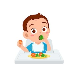 Il piccolo bambino sveglio mangia frutta e verdura