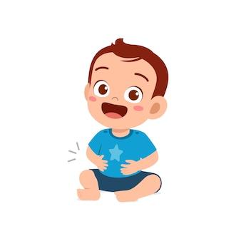 Il piccolo bambino carino si sente pieno dopo aver mangiato e toccato lo stomaco