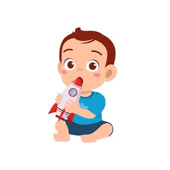 Piccolo neonato sveglio che gioca con il razzo