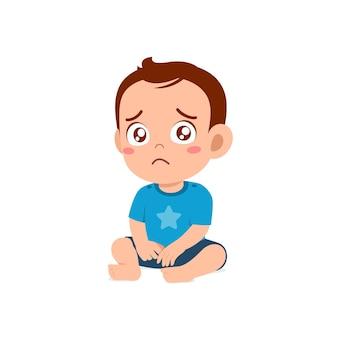 Il piccolo bambino sveglio mostra l'espressione triste e piange