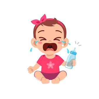 Piccola neonata sveglia che piange tenendo una bottiglia di latte vuota milk