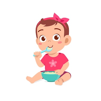 La piccola neonata sveglia mangia il porridge in ciotola con il cucchiaio