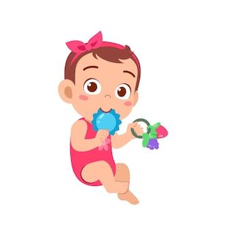 Piccola neonata sveglia che gioca con il giocattolo da masticare